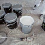 peintre ouvre un pot de peinture airless